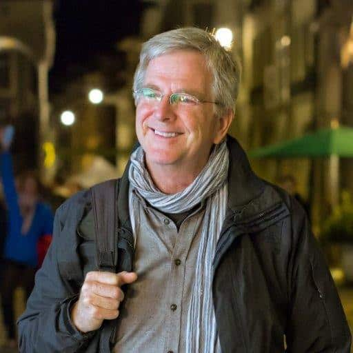 Rick Steves smiling and carrying a bag